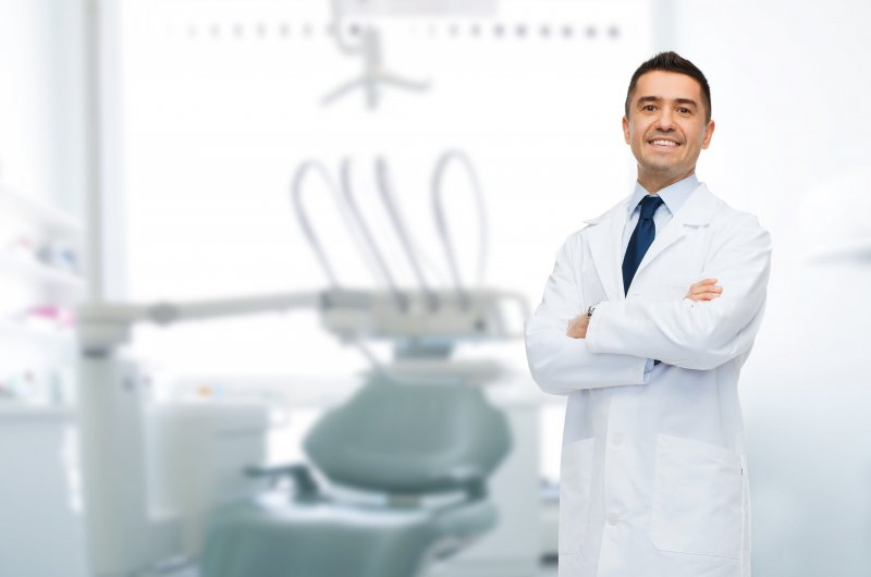 a male dentist standing with his arms crossed and smiling while wearing a lab coat in a treatment room